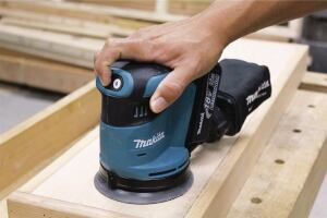A push-button switch starts the tool and toggles through high, medium, and low speeds (the other button stops the tool). The sander takes 5-inch 8-hole hook-and-loop disks.