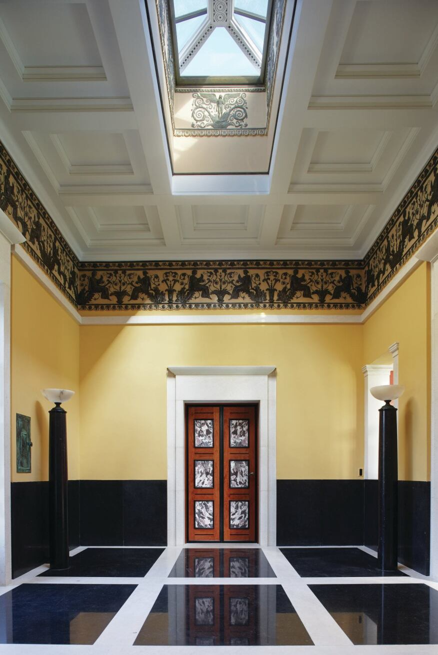 The yellow-toned entrance hall, with its marble detailing, is meant to provide a contrast against the austere materiality of the exterior.