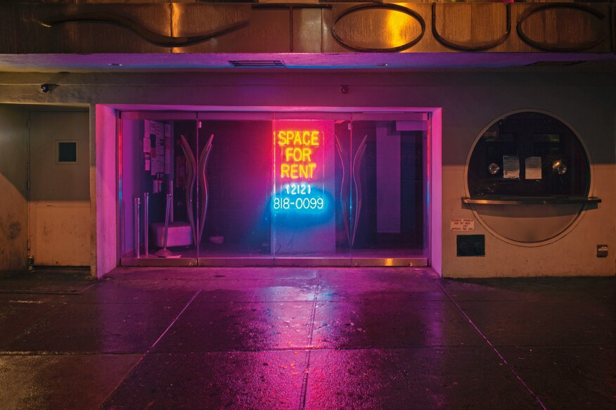 """Neon Sign, West 50th Street, New York""""A glowing light drew my attention at the intersection, because the entire block was quite dark due to the several vacant stores. The sign appealed to me because of the cheerful colors and glowing neon light. Normally, I might not have paused to look at this place, but the pink and blue light allowed me to concentrate on the basic architectural structure of the storefront. Without products, normal signage, or mannequins in the window, I could see the place in its own glory."""" -- Lynn Saville"""