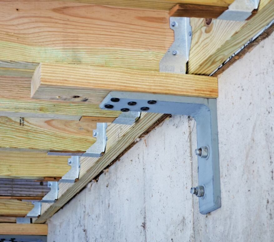 Sometimes blocking is required to avoid installing concrete anchors too close to a foundation edge. In those cases, the author uses 6-inch instead of 4 1/2-inch-long HeadLOK screws to attach the bracket to the doubled joists. The bracket in the photo was fabricated from 1/2-inch-thick angle iron (the steel was manufactured as a 16-foot-long angle bar with two 8-inch flanges). While the steel is much thicker than necessary, it was readily available, and the fabricator could just cut off 3-inch-wide pieces of the angled steel.