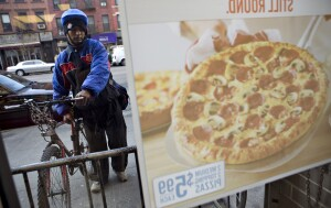 Hossain Md prepares to make a delivery from a Domino's Pizza franchise on 89th Street in New York, U.S., on Wednesday, Jan. 13, 2010. Domino's Pizza Inc., the second-largest U.S. pizza maker, said Internet orders make up the fastest-growing part of its business, accounting for as much as 30 percent of sales in some markets. Photographer: Daniel Acker/Bloomberg via Getty Images