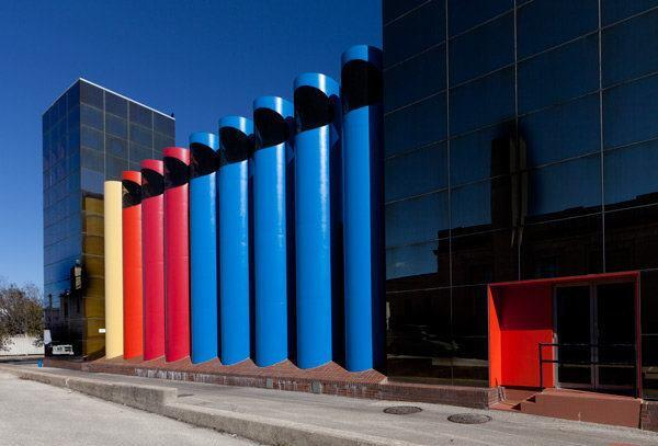 Nine brightly colored ventilation ducts liine a rear alley behind the facility.