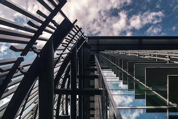 A view skyward shows fixed sunshades on the building's south façade (right), with vertical, aluminum reeds to block  solar gain on the west façade (left).
