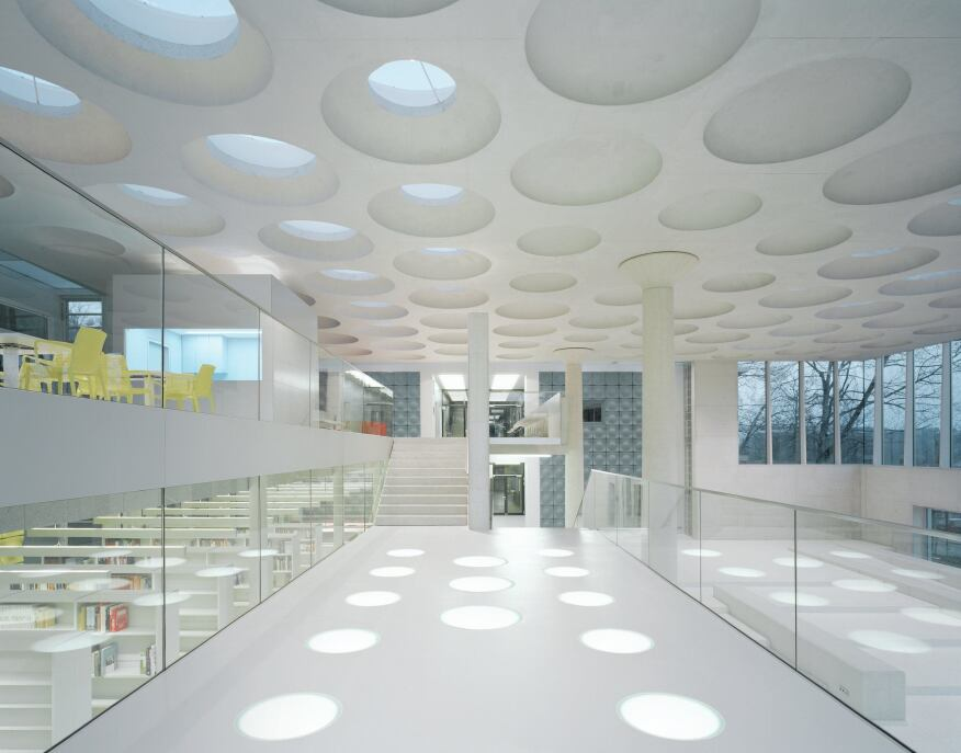 The interior of the addition connects various levels of the surrounding buildings. A walkway overlooks the assembly hall on one side, and the student café, with its yellow twin chairs from Brunner, and library, on the other. Circular floor lights mimic the coffers and skylights in the concrete ceiling.