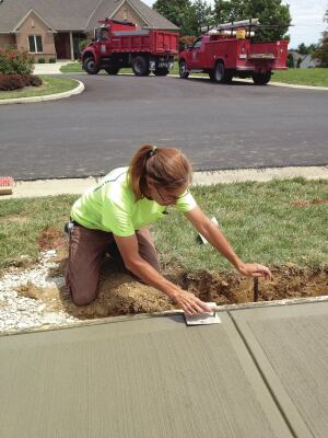 Pam Frank puts the finishing touches on a concrete sidewalk panel.