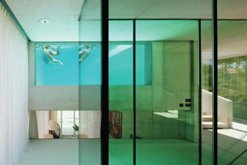 Glazed walls on the first floor offer views into the living area below and the pool above.
