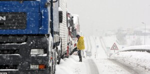 A driver waits outside his truck as vehicles stuck on a snowed up national road on December 2, 2010 near Cherbourg, western France, after heavy snow and freezing temperatures severely hit Europe. Snow and ice in France forced hundreds of drivers to abandon their cars, caused major disruption to flights at Paris airports and shut down half of Eurostar trains to London. AFP PHOTO/KENZO TRIBOUILLARD (Photo credit should read KENZO TRIBOUILLARD/AFP/Getty Images)