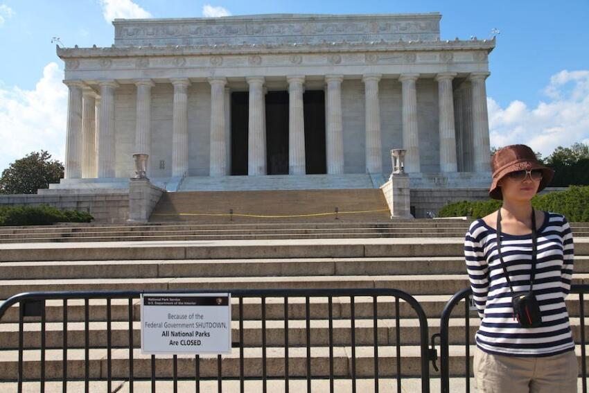 A tourist poses in front of the closed Lincoln Memorial.