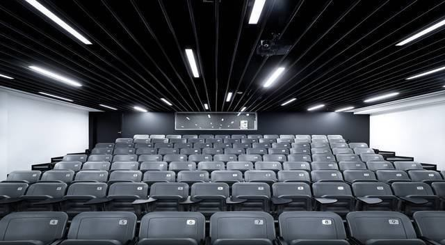 The auditorium uses 4-foot-long 28W T5 linear fluorescent fixtures set on a DALI control system to meet the AV needs of the space.