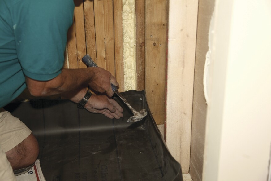 After the membrane is placed in the shower, carefully fold the excess in the corner, keeping it as flat as possible, and secure the folds with a nail at least 2 inches above the threshold.