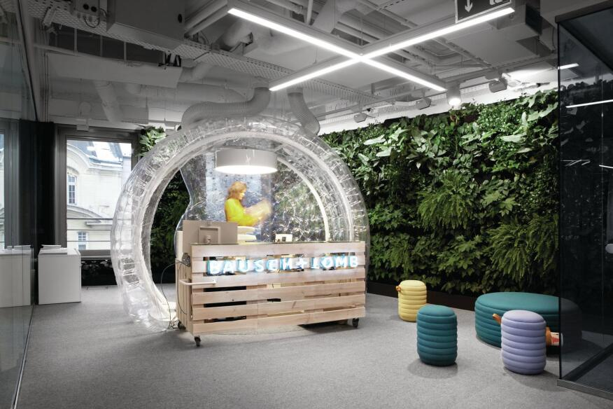 The pine-slat reception desk at the new Bausch + Lomb offices in Warsaw, Poland, is encased in an inflated vinyl bubble.