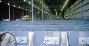 Preparation for the 380x115-ft. floor placement included two-way PT tendons. Note the tendons pass through a support channel for vertical storing dock leveler and trucks are tailgating concrete.