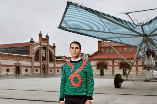 "Andrés Jaque poses in front of his firm's ""Escaravox"" project. Jaque purchased a series of winged rolling irrigation platforms, added speakers, wiring and lighting, and staged them in a public square in Madrid. Musicians, DJs, writers, and actors used them to plug in equipment and hold impromptu readings and performances."