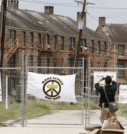 A man photographs the shuttered St. Bernard low-income housing project in July 2006, almost one year after Hurricane Katrina flooded this area of the city. New Orleans public housing residents recently filed a civil rights lawsuit against the city's housing authority and HUD.