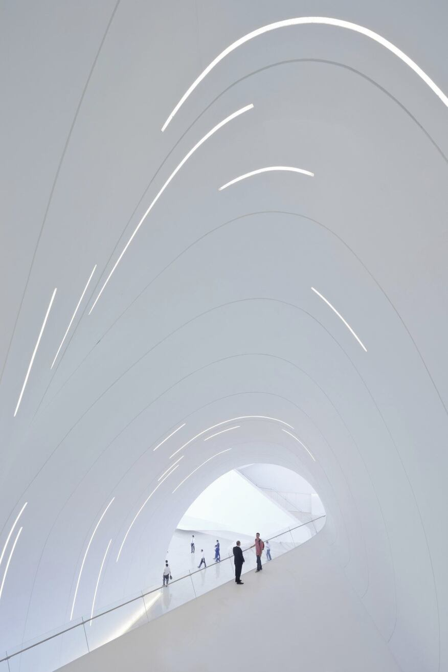 Within the center, slits along the interior's curved surfaces provide general illlumination while amplifying the vertiginous effect of the distorted spaces.
