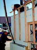 Walls built with four different manufactured ICF products demonstrated how the ICF process works. Shown here is a worker placing concrete through a ledge that will support a brick facing wall.