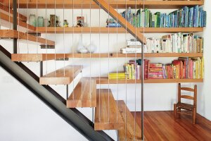 Creative use of old wall studs converted into stair treads and bookshelves