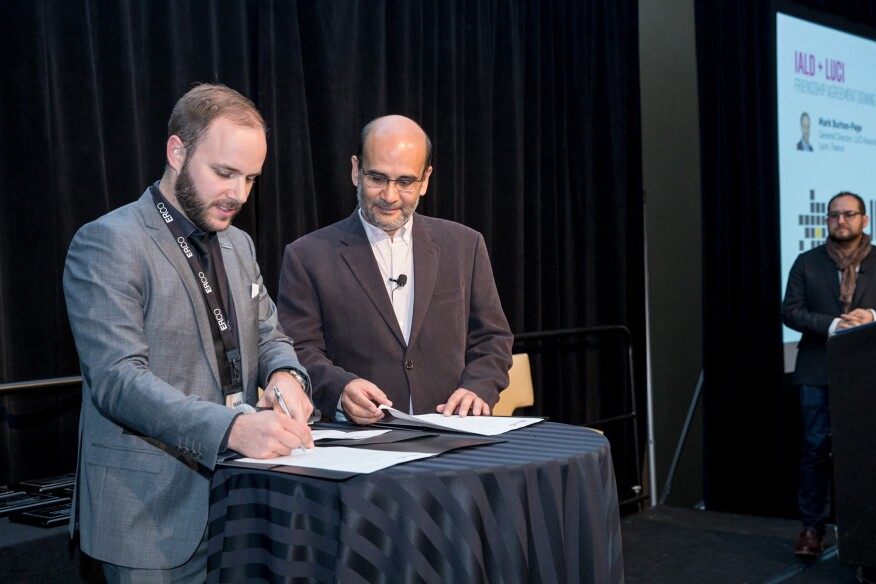 Mark Burton-Page, General Director of LUCI (left) and Victor Palacio, 2016-2017 IALD President (right) sign a Friendship Agreement during the IALD Enlighten Americas conference in Denver. Incoming IALD President David Ghatan (far right) looks on.