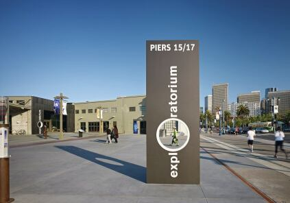 The expanded, punched-out 'O' in the Exploratorium sign turns pedestrians into exhibits in the public plaza outside the new museum space.