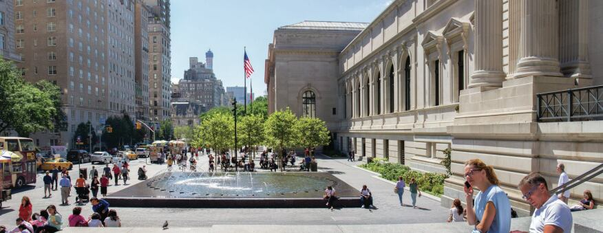 A view of the plaza during the day. This outdoor public space, which runs the length of four city blocks along Fifth Avenue, features new granite fountains, paving, lighting, and seating. The plaza also features allées and bosques of London Plane trees at the north and south ends that help lead visitors to the museum's main entrance.