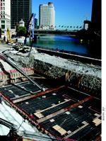 Right: The mat-slab is approximately 15 feet away from the Chicago River in downtown Chicago and about 15 feet below the water's surface. The mat rests on caissons and pile caps and is believed to be the largest SCC placement to date. Above: All of the 4700 cubic yards of SCC concrete were placed by conveyor and flowed approximately 40 feet from the point of placement. The 22 hours of placement time were completely uneventful, to the delight of all concerned.