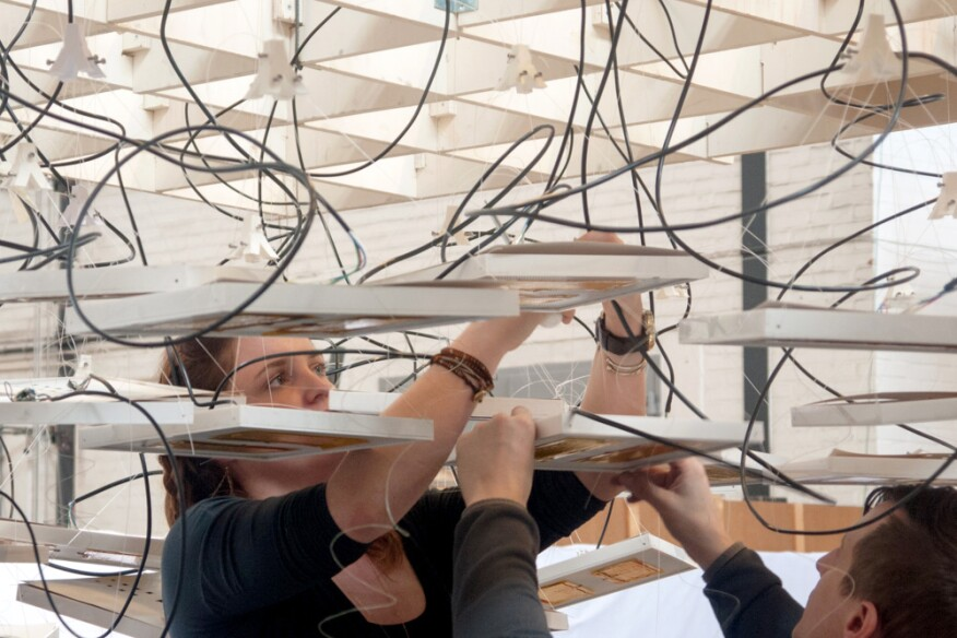 Annie Scherer and Aaron Zeligs from Atmospheric Delight suspend heating and lighting panels above their installation.