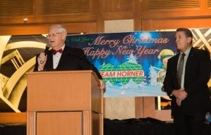 Bill Kent, president/owner of Team Horner, addresses employees at a recent holiday function. In April 2015, he'll step down as president to become chairman of the board. Mike Dooley (right) will succeed him.