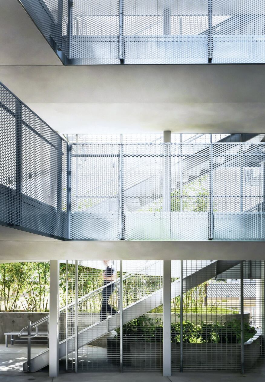 Much of the circulation in the building is accommodated by open-air pathways, with railings of perforated aluminum that nod to the building's skin.