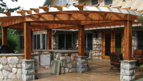 A western red cedar pergola by Creative Outdoor Wood Products, Fenton, Mich., tops stonework that was subbed out by the homeowner.