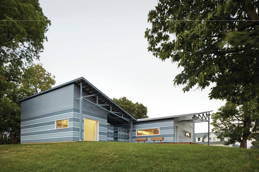 The house and garage are clad in a cement board panel rainscreen.