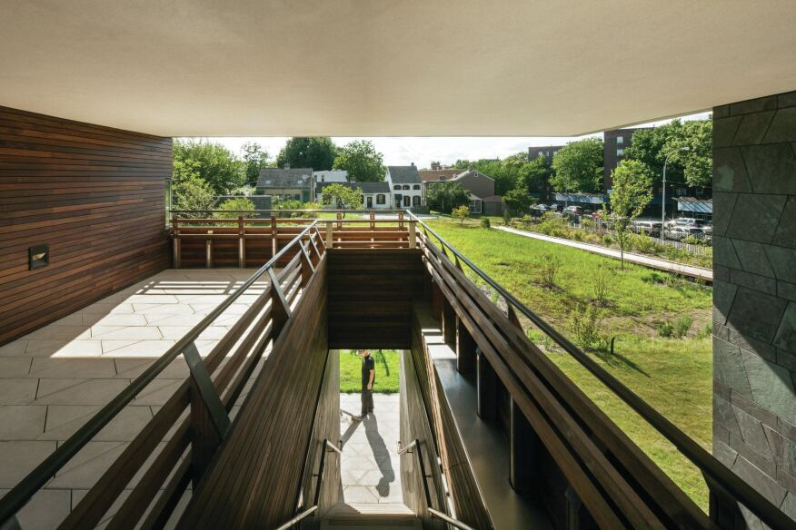 An open-air staircase grants access from a covered porch on the second floor down to the core of the historic site. The porch overlooks the historic Weeksville homes on the far side of the site.