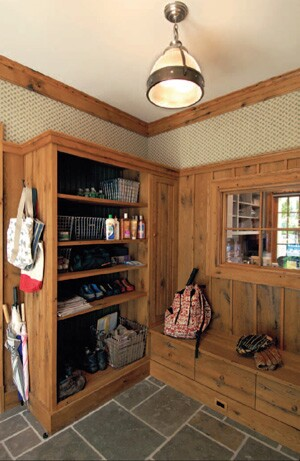 The mudroom, off the other side of the kitchen, includes a cupboard where the children can store coats and boots, as well as a storage bench to hold other outdoor gear. The storage units are made from reclaimed wood. A small window in the mudroom provides a view into the adjacent home office, which is fitted with custom cubbyholes to hold supplies and paperwork.