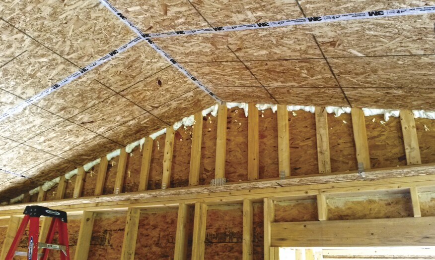 After attaching OSB to the underside of the scissors trusses and sealing the seams with tape, the author's crew foamed the gaps in the gable end wall to contain blown insulation.