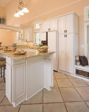 The clients needed to maximize storage in this townhouse kitchen. The island has two pedestal legs that hide 12-inch-deep storage cabinets. One panel on each leg is an operable door.