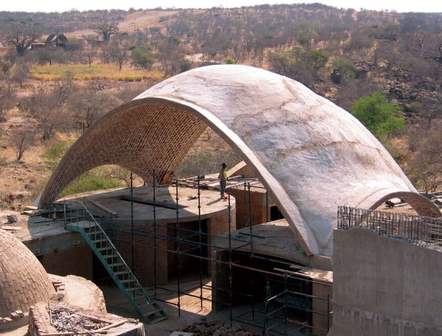 The Mapungubwe National Park Interpretive Centre is sustainable in many ways. Among them: (1) The vaults are composed of locally made stabilized earth tiles and designed to be structurally sound with a minimum use of material and at the lowest cost possible; (2) the tiles' high thermal mass passively cools spaces and radiates heat at night; (3) as part of the project's Poverty Relief Program, the structures are being built by locals trained in a masonry technique that is quickly and easily learned.
