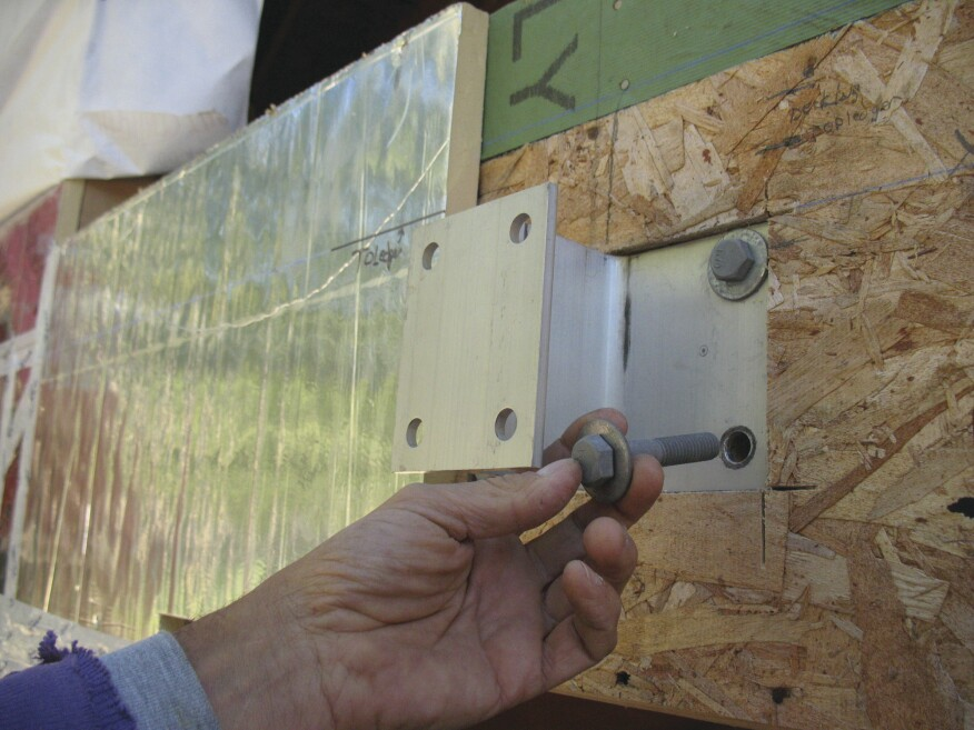 Maine Deck Brackets are bolted directly to the rim joist, so the first step is to cut out the wall sheathing and through-bolt the wider flange to the rim.