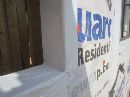 "Jamb flashing. For the jamb flashing, I recommend installing a straight peel-and-stick flashing adhered to the housewrap on the face and to the wood in the rough opening. Where the jamb flashing laps the sill flashing, the lap is not perfect (there are still wrinkles) but it is sufficient; any water that finds its way to the flashing will ""shingle off."" Once the jamb flashing is in place, the window is installed with the flanges caulked (just not at the sill) and fastened to the wall."