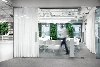 The conference room, which is one of the few enclosed spaces in the floor plan, features glass walls that can be closed off by opaque curtains.