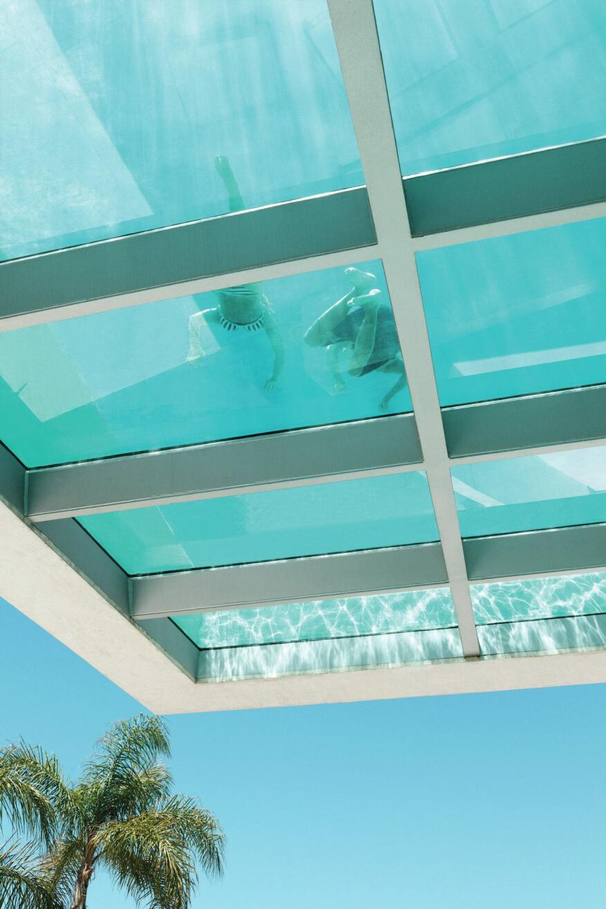 The underside of the cantilevered pool structure is glazed, allowing sunlight to filter through the water to the entry ramp and adjacent terrace below.