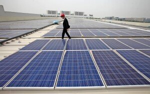 --FILE--A Chinese inspector examines solar panels at a rooftop photovoltaic power station in Tianjin, China, 13 May 2014.  The Commerce Department on Tuesday (3 June 2014) imposed steep duties on importers of Chinese solar panels made from certain components, asserting that the manufacturers had benefited from unfair subsidies. The duties will range from 18.56 to 35.21 percent, the department said. The decision, in a long-simmering trade dispute, addresses one of the main charges in a petition brought by the manufacturer SolarWorld Industries America. While it is preliminary, the ruling means that the United States will begin collecting the tariffs in advance of the final decision, expected later this year.