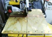 A plywood table clamped to the tile saw's bed.