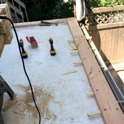Because the curb establishes the final elevation for the rooftop deck, great care was taken to shim the second 2x10 layer so that it would be absolutely flat and level in every direction. 4 1/2-inch-long structural screws were used to fasten the 2x10 layers to the roof framing and to each other.