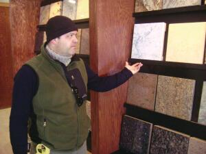 Newcomer points out granite product samples. Before shopping with a client, he uses computer images to help them visualize their remodeled space. He also asks them to bring cabinet doors, paint colors, and design ideas along with them to the showroom.