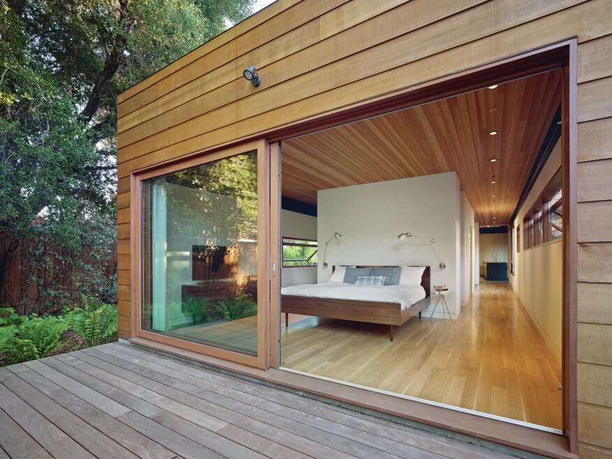 The master bedroom, in the eastern end of the house, features a white oak floor and Douglas Fir ceiling, and sliding panels that open onto a private deck.