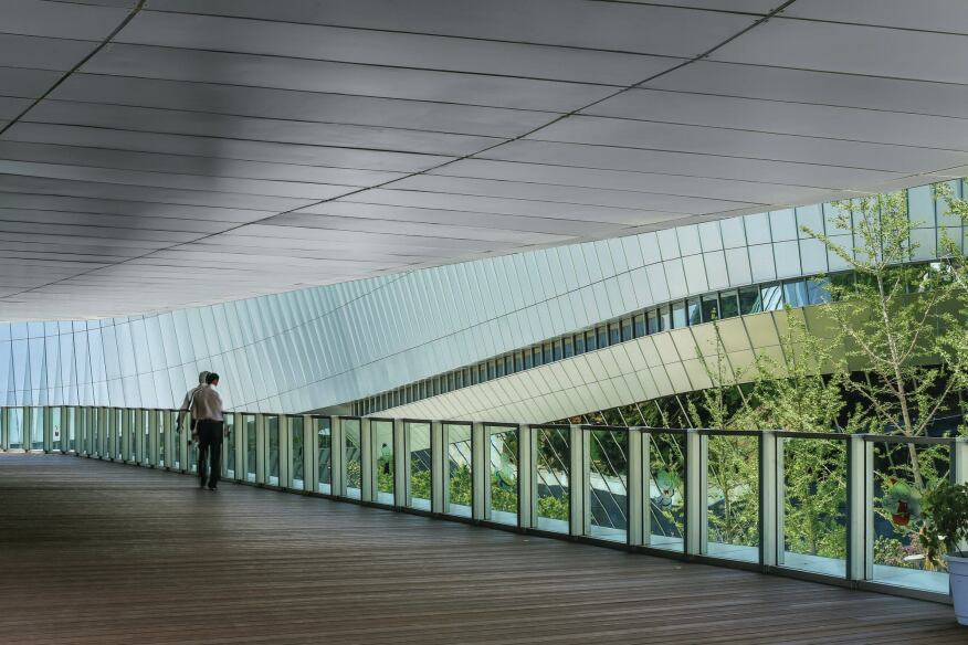 The inset walkways' metal ceiling and wood floor frame views of the surroundings.