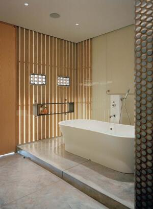 Wood screens add warmth, texture, and natural light to the minimalist master bath. Polished concrete floors reflect light back up into the room.