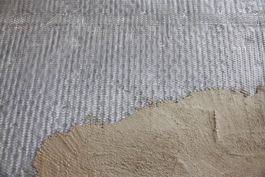 """The first coat of traditional stucco is called the """"scratch coat."""" This coat tooths into the lath and holds it onto the building. You can see here that the fabric on the Delta Dry Stucco & Stone keeps the stucco from clogging the pores of the drainage mat."""