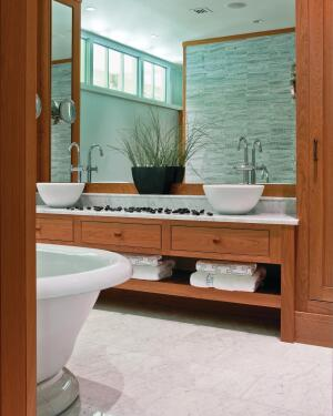 A symmetrical layout and abundant clerestory light give this master bath its serene sense of order. Watery green mosaic tile set in a sinuous pattern backdrops the freestanding vessel tub.
