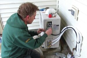 ReVision Energy's Dave Ragsdale connects the control circuit of the outdoor unit of a 1-ton Fujitsu mini-split on a home near Portland, Maine. In combination with a wood stove, the mini-split will mostly idle the home's existing oil boiler, except during the coldest part of the year.