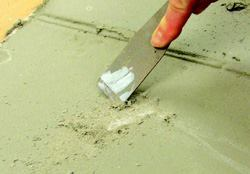The weak laitance layer—typical of acrylic modified, portland-based, and calcium aluminate-based cementitious resurfacers—should be removed prior to topcoating with high performance coatings.